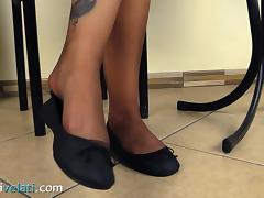 Dark-haired cutie smokes a cigarette and exposes her attractive legs