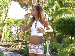 Cute curly haired chick fingering her pussy in the garden