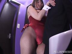 An Asian girl in a playboy bunny costume sucks a dick